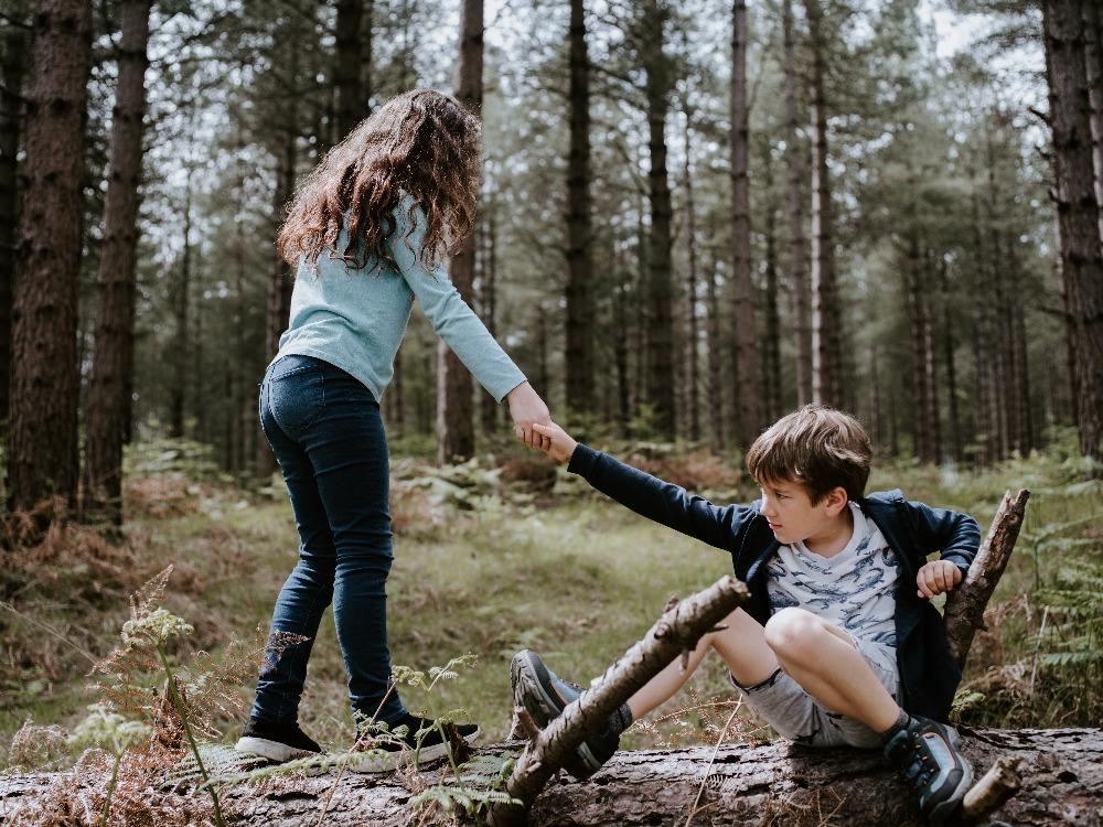 girl helping boy up
