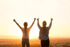 two women raising arms at sunrise