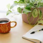 blank notebook on a desk with a plant and mug