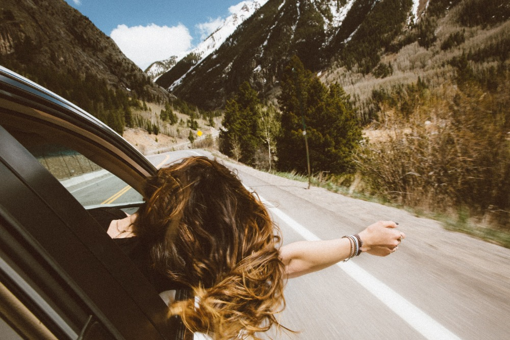 woman leaning out the window of a car driving through the moutains