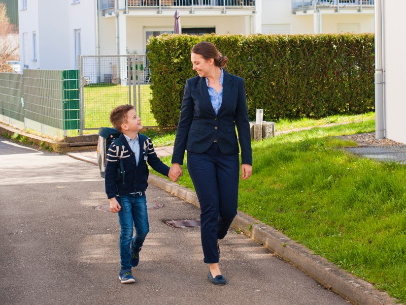 business-owning mom walking son home from school